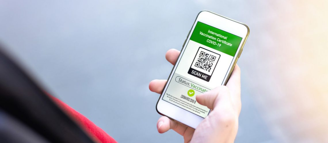 Male hand holding a smartphone with International Vaccination Certificate COVID-19 QR code